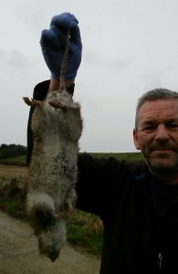 Picture of Terry Walker from TP Pest Control Services holding a rat that was caught by Max the Terrier.